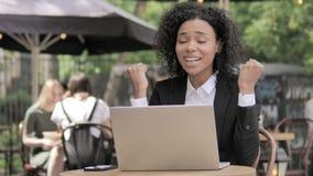 庆祝在室外咖啡馆的膝上型计算机的非洲女实业家 影视素材
