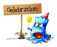 庆祝在木标志附近的一个蓝色妖怪 免版税图库摄影