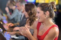 庆祝在老虎机的妇女胜利在赌博娱乐场 库存图片