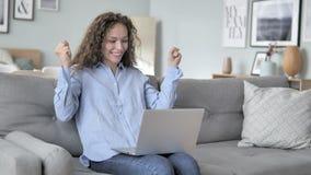 庆祝在膝上型计算机的卷发妇女成功