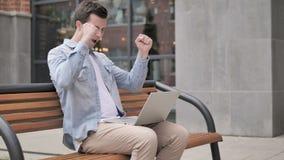 庆祝在膝上型计算机的年轻人坐在办公室外