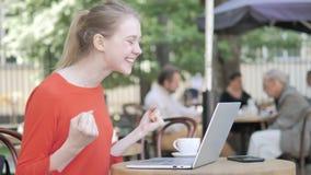 庆祝在膝上型计算机的年轻女人坐在咖啡馆大阳台 股票录像