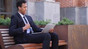 庆祝在膝上型计算机的激动的非洲商人成功坐长凳 股票视频