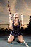 庆祝在膝盖的女性网球员 图库摄影