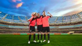 庆祝在足球的三位女性足球运动员胜利被归档 免版税库存图片