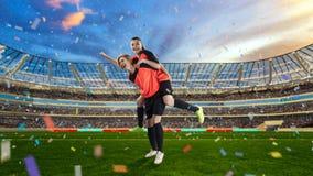 庆祝在足球的两位女性足球运动员胜利被归档 免版税图库摄影