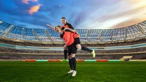 庆祝在足球的两位女性足球运动员胜利被归档 免版税库存图片