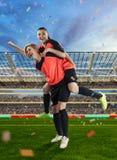 庆祝在足球的两位女性足球运动员胜利被归档 库存照片