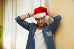 庆祝在他的红色圣诞老人帽子的偶然年轻人圣诞节 免版税库存照片