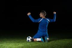 庆祝在黑背景的足球运动员胜利 库存图片