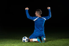 庆祝在黑背景的足球运动员胜利 免版税图库摄影