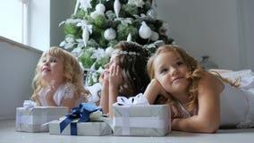 庆祝大气,有卷发的小女朋友作梦在背景圣诞树的礼物附近的与 影视素材
