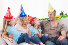 庆祝孪生生日的家庭坐长沙发 免版税库存照片