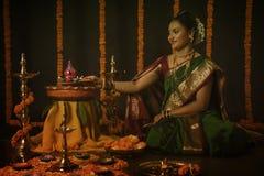 庆祝屠妖节节日的印地安妇女画象通过点燃灯 库存照片