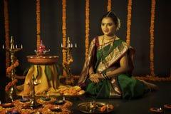 庆祝屠妖节节日的印地安妇女画象通过点燃灯 免版税库存图片