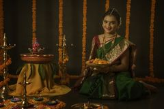 庆祝屠妖节节日的印地安妇女画象通过点燃灯 免版税图库摄影