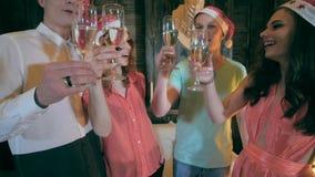 庆祝庆祝圣诞节女儿帽子母亲圣诞老人佩带 拿着杯香槟的朋友做多士欢呼 关闭 影视素材