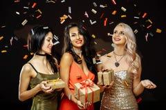 庆祝庆祝圣诞节女儿帽子母亲圣诞老人佩带 有圣诞节礼物的朋友 新年度当事人 免版税图库摄影