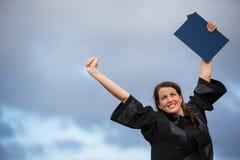 庆祝快乐她的毕业的俏丽,少妇 免版税图库摄影
