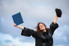 庆祝快乐她的毕业的俏丽,少妇 免版税库存图片