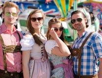 庆祝慕尼黑啤酒节的小组愉快的朋友 免版税库存图片
