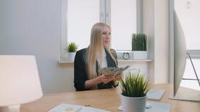 庆祝成功的妇女在办公室 在举行在手捆绑的工作场所的典雅的白肤金发的女性开会现金看 股票视频
