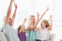 庆祝成功的家庭,当看电视时 免版税图库摄影