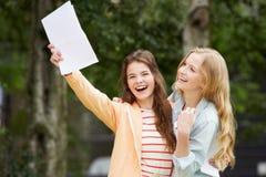 庆祝成功的检查结果的两个十几岁的女孩 免版税库存照片