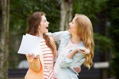 庆祝成功的检查结果的两个十几岁的女孩 库存图片