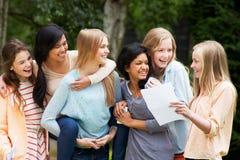 庆祝成功的检查结果的六个十几岁的女孩 免版税库存照片