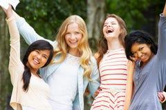 庆祝成功的检查结果的四个十几岁的女孩 免版税库存照片