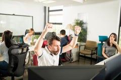 庆祝成功的激动的商人在办公室 免版税库存图片