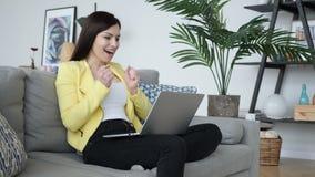 庆祝成功的激动的妇女,研究膝上型计算机 股票录像