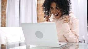 庆祝成功的激动的美国黑人的妇女,当研究膝上型计算机,坐长沙发时 股票视频