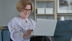 庆祝成功的激动的老资深妇女,研究膝上型计算机 影视素材