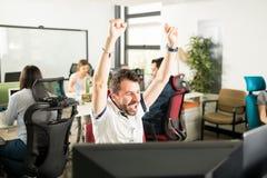 庆祝成就的商人在起始的办公室 图库摄影
