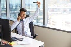 庆祝打电话的商人在书桌在办公室 免版税库存照片