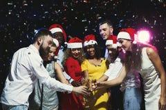 庆祝新年用香槟的小组青年人在夜总会 免版税图库摄影