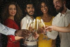 庆祝新年用香槟的小组青年人在夜总会 免版税库存照片