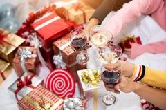 庆祝新年聚会的人的手在有喝酒玻璃和当前背景的家 新年和圣诞派对 免版税库存图片