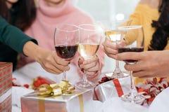 庆祝新年聚会的人的手在有喝酒玻璃和当前背景的家 新年和圣诞派对 库存照片