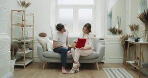 庆祝某一专辑,在家,在沙发人的有吸引力的夫妇给夫人的一件礼物,她是很愉快的 股票视频