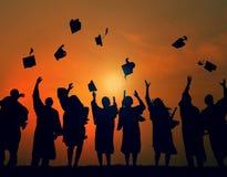 庆祝毕业剪影概念的小组学生 免版税库存图片