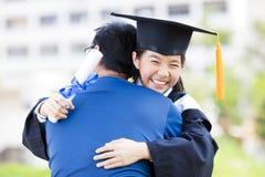 庆祝毕业的学生和家庭拥抱 免版税库存照片