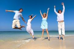 庆祝海滩夏天概念的两对夫妇 库存图片
