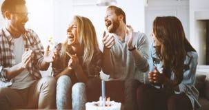 庆祝生日的年轻小组愉快的朋友 免版税库存照片