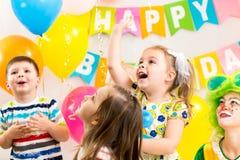 庆祝生日聚会的快活的孩子小组 免版税库存图片