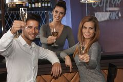 庆祝用在酒吧的香槟的青年人 免版税库存图片