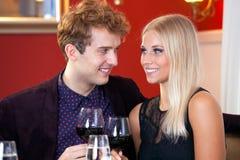 庆祝用红葡萄酒的愉快的夫妇 免版税库存图片