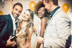 庆祝用香槟的小组妇女和人 免版税库存照片